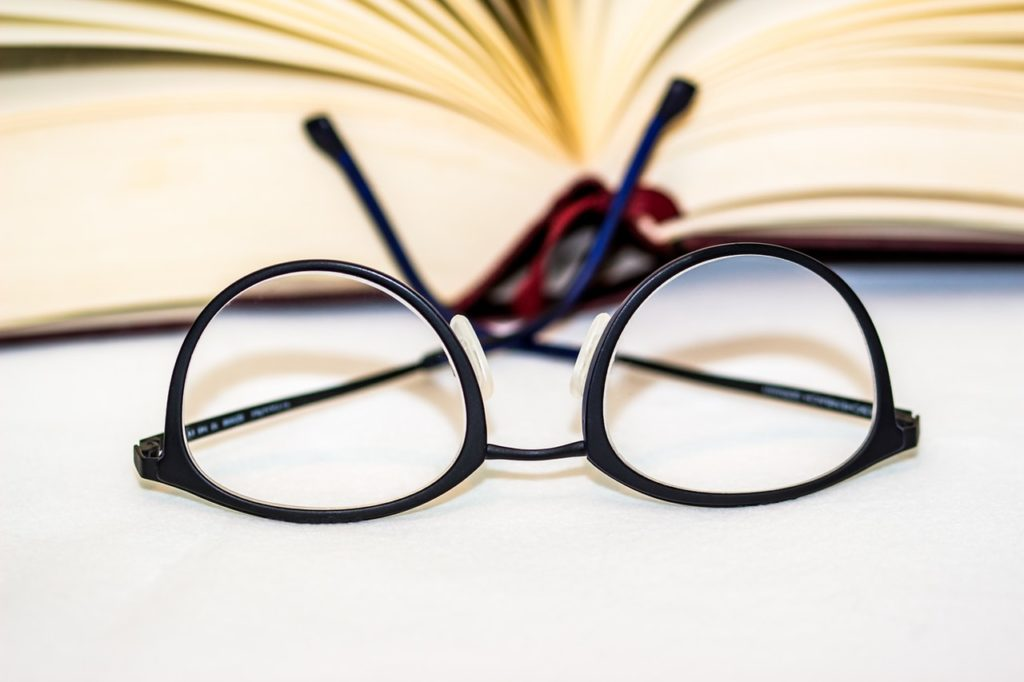 Glasses next to an open book.