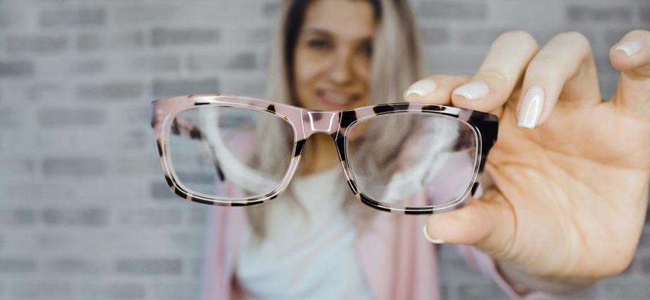 Picture close up of a blonde hair lady holding glasses in her hand.